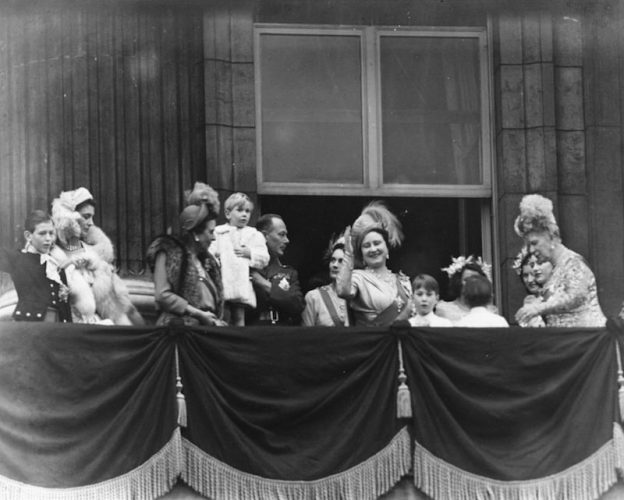 The queen's wedding guests waving from a balcony.