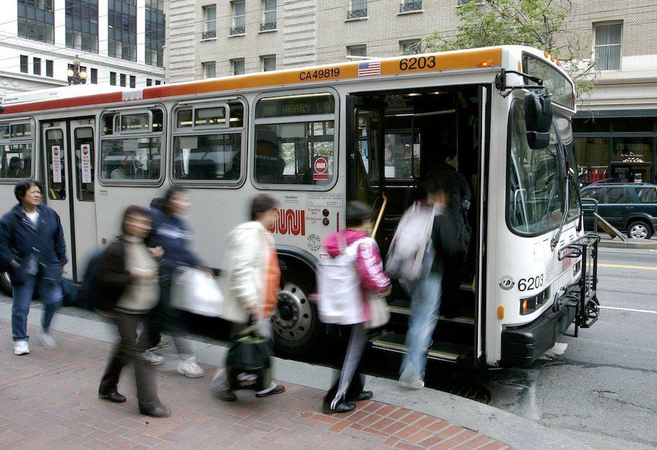 Passengers board a MUNI bus along Market Street
