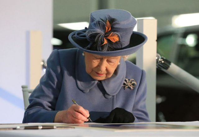 Queen Elizabeth signing papers on a desk.