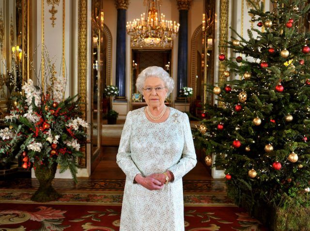 Queen Elizabeth stands in front of a Christmas Tree in a decorated hall.