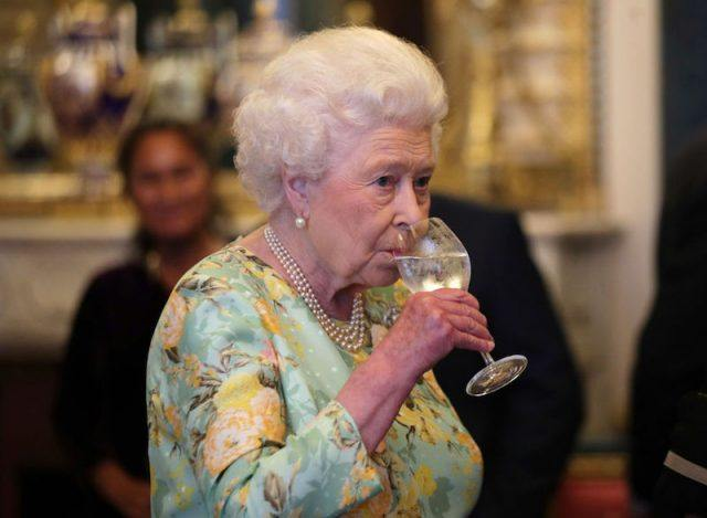 Queen Elizabeth drinking water from a glass.