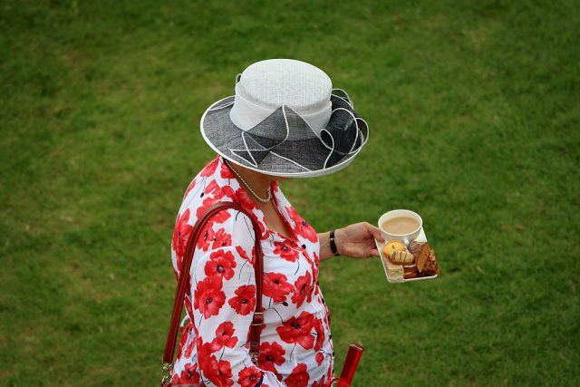 Queen Elizabeth walks outdoors with a plate of tea and biscuits.