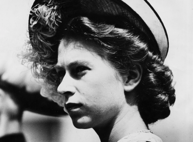 Princess Elizabeth walks outdoors while wearing a hat.