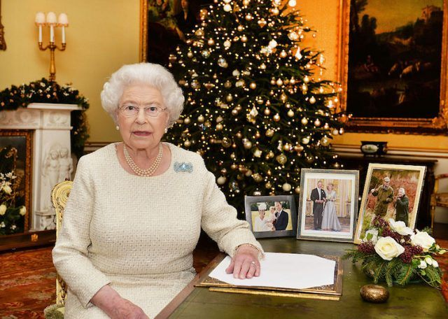 Queen Elizabeth sits at a desk surrounded by Christmas decorations.