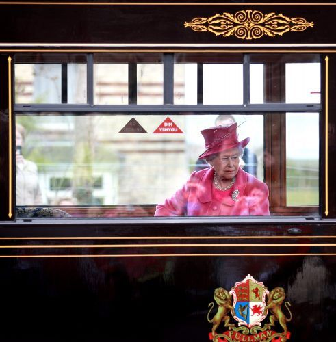 Queen Elizabeth riding a train.