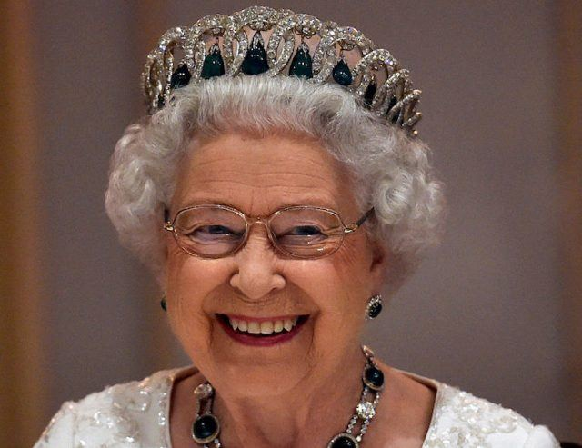 Queen Elizabeth smiles while wearing a jeweled crown and jewelry.
