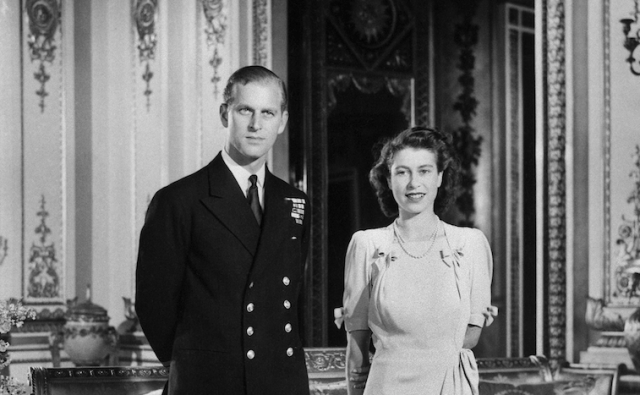 Queen Elizabeth and Prince Philip standing in large decorated room.