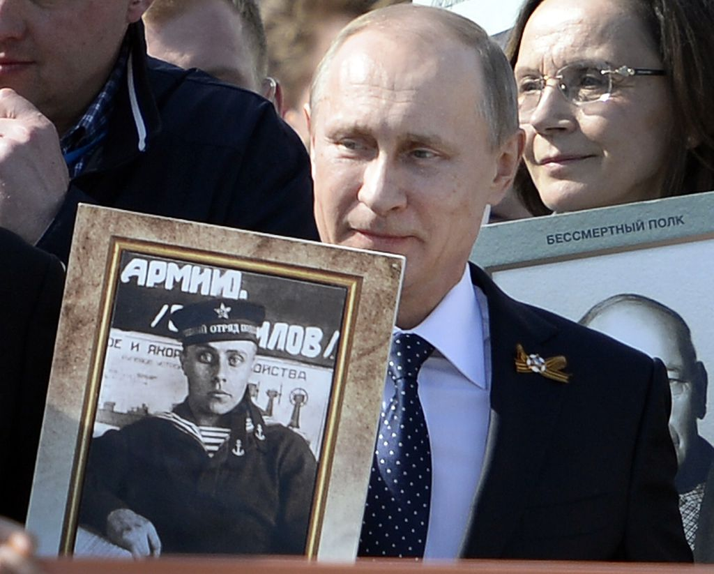Russian President Vladimir Putin holds a portrait of his father