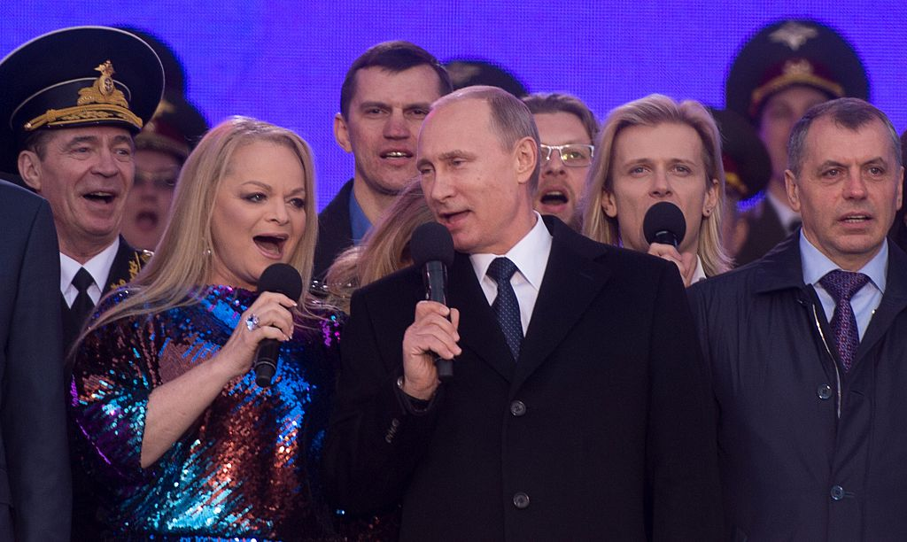 Russia's President Vladimir Putin (C), Russian pop singer Larisa Dolina (2ndL) and Crimean parliament speaker Vladimir Konstantinov (R) sing the Russian national anthem
