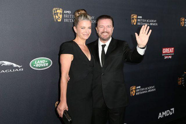 Ricky Gervais and Jane Fallon posing for photographers on a red carpet.