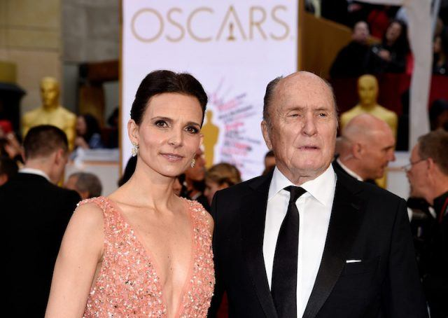 Robert Duvall and Luciana Pedraza posing for photos at the Oscars.