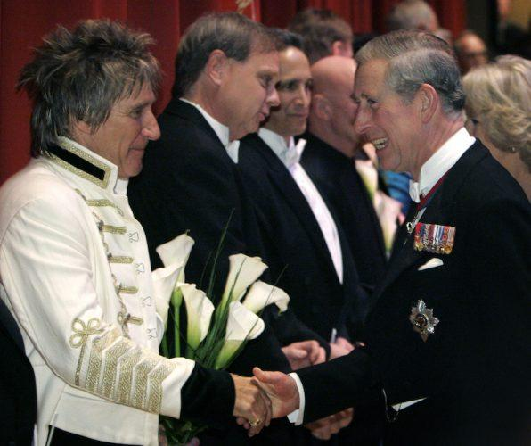 Prince Charles shakes hands with Rod Stewart.