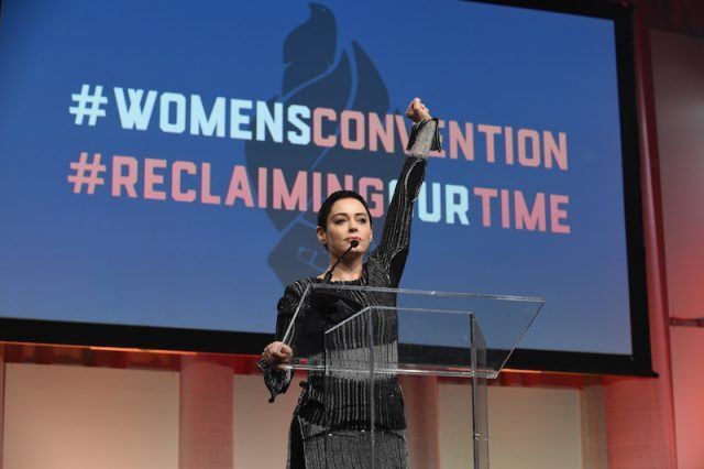 Rose McGowan leading a conversation on stage in front of a podium.