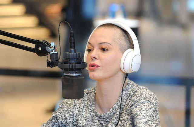 Rose McGowan speaking into a black microphone while wearing white headphones.