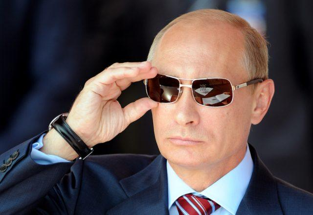 Russian Prime Minister Vladimir Putin adjusts his sunglasses as he watches an air show.