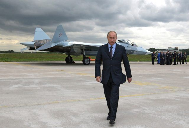 Russian Prime Minister Vladimir Putin walks near a new Russian fighter jet Sukhoi T-50.