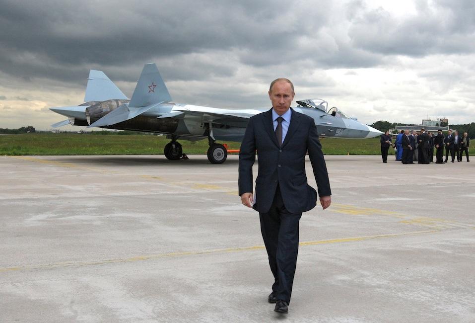Russian Prime Minister Vladimir Putin walks near a new Russian fighter jet Sukhoi T-50