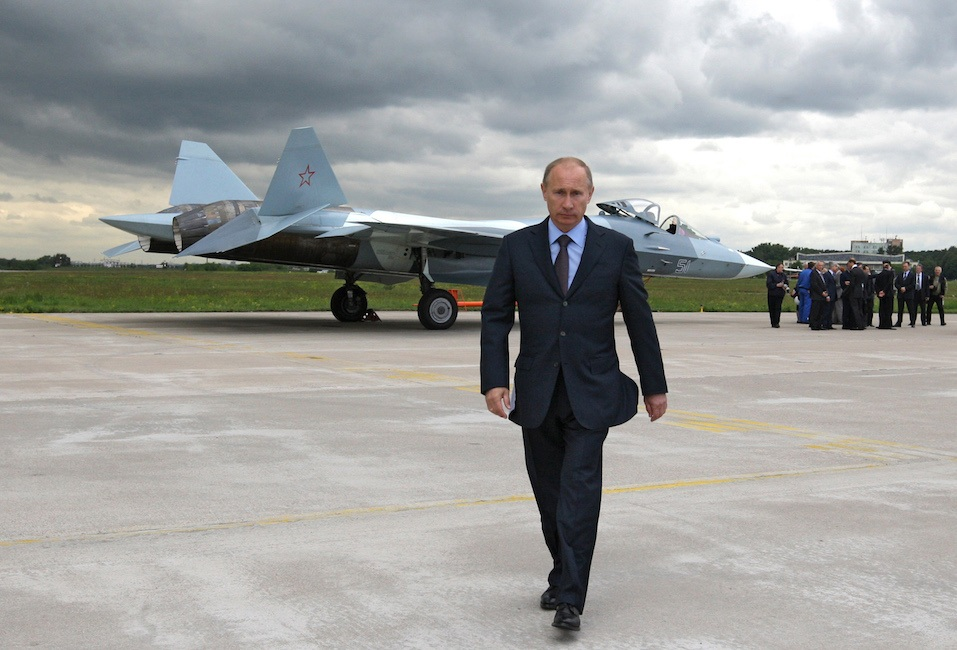 Russian Prime Minister Vladimir Putin walks near a new Russian fighter jet Sukhoi T-50