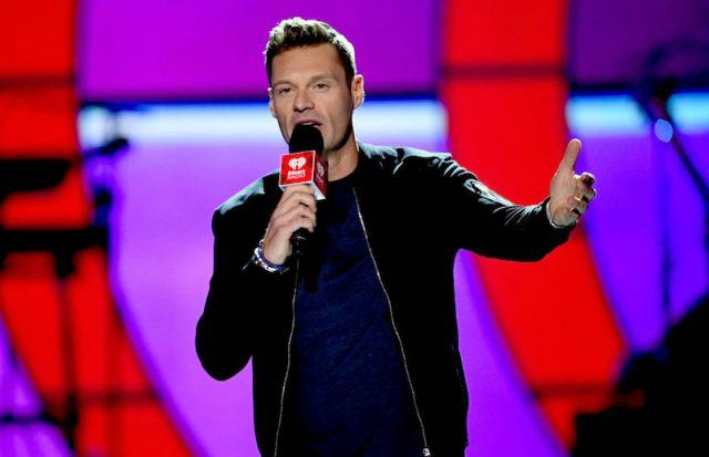 Ryan Seacrest holding a microphone.