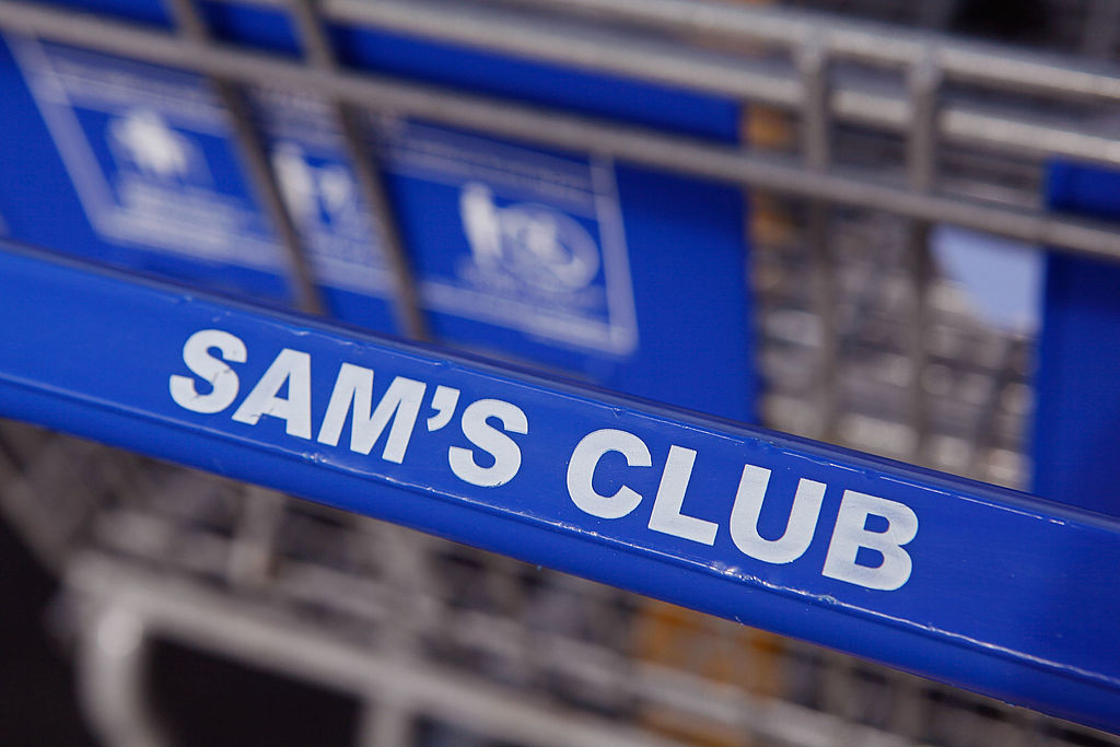 A shopping cart sits in the parking lot of a Sam's Club