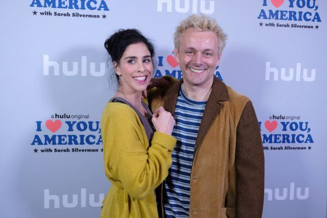 Sarah Silverman and Michael Sheen smile brightly while posing for photographers.