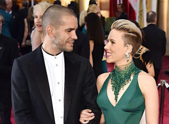 Scarlett Johansson and Romain Dauriac smile as they look at each other.