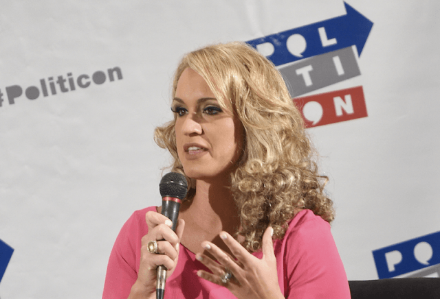 Scottie Nell Hughes speaks into a microphone while addressing an audience.