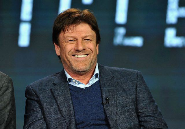Sean Bean smiling while on a panel on stage.