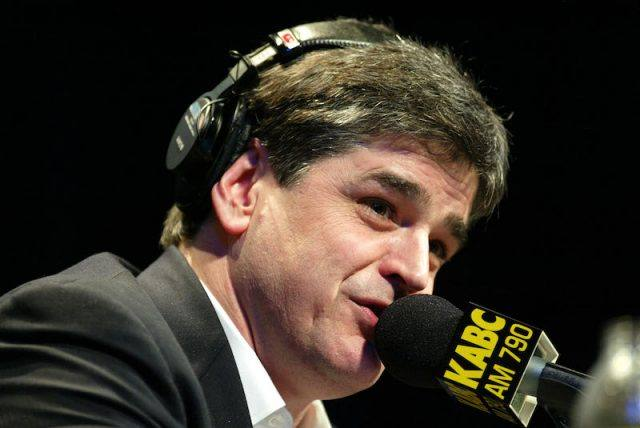 Sean Hannity speaking into a black microphone while wearing headsets.