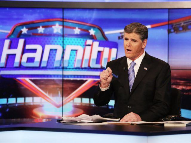 Sean Hannity holding a pen while sitting behind a news desk.