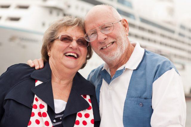 A senior couple smiles while standing in front of a ship.