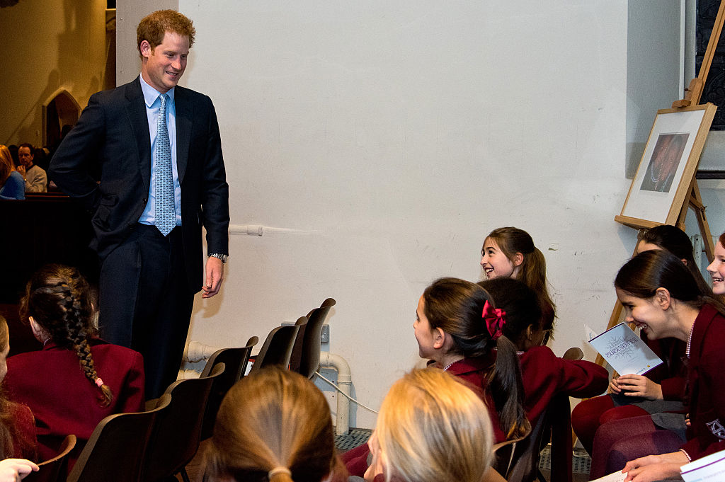 Prince Harry interacts with children in a choir.