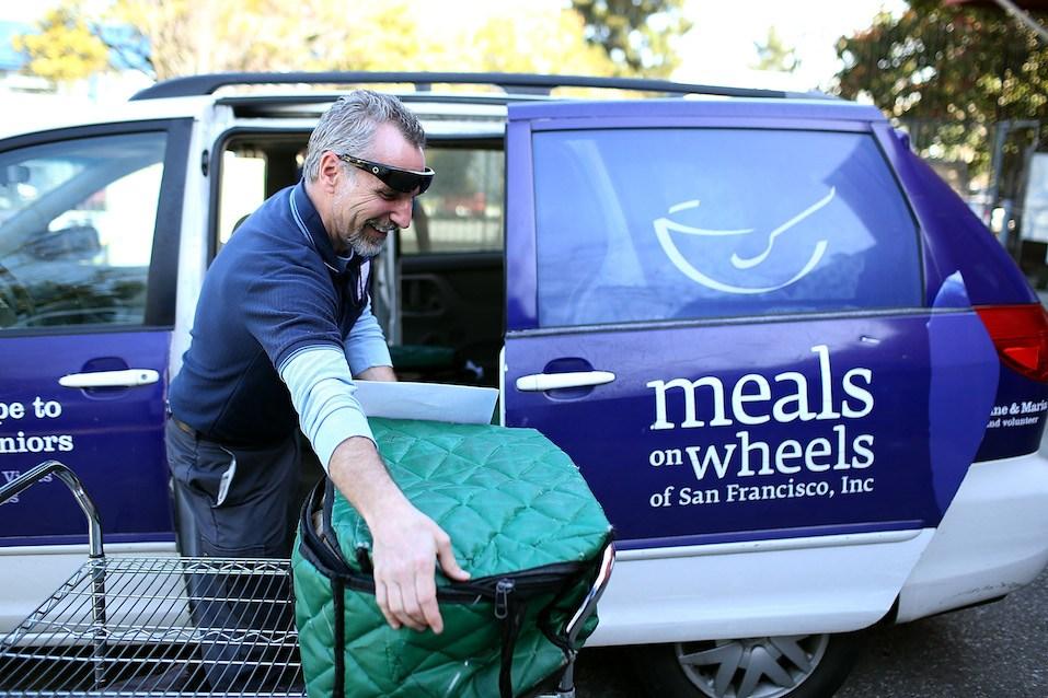 Meals On Wheels of San Francisco driver Jim Fleming loads meals into a van