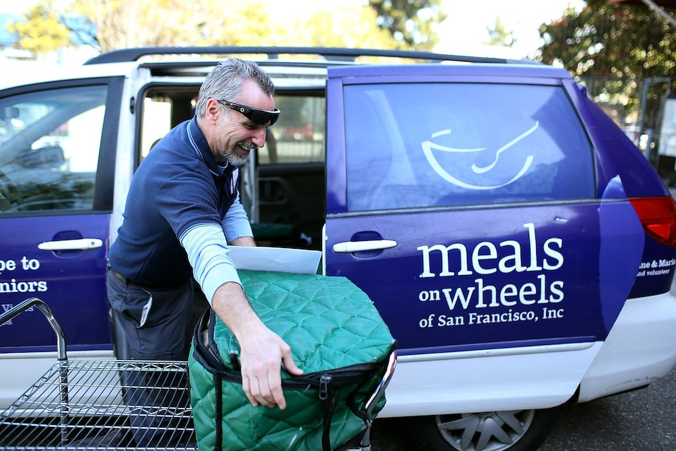 Meals On Wheels of San Francisco driver Jim Fleming loads meals into a van