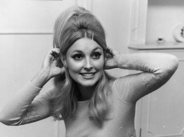 Sharon Tate smiles while holding her hair.