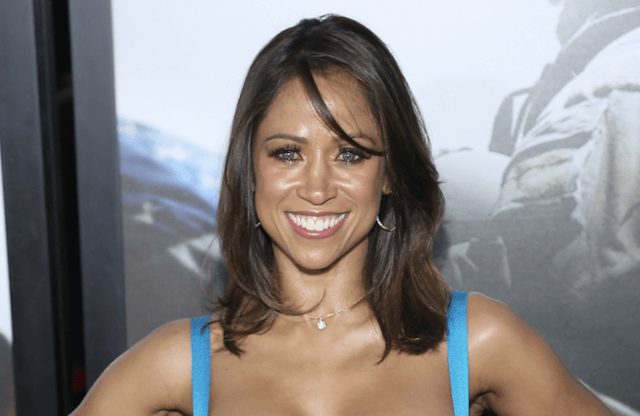 Stacey Dash smiles brightly while posing for photographers in a blue dress.