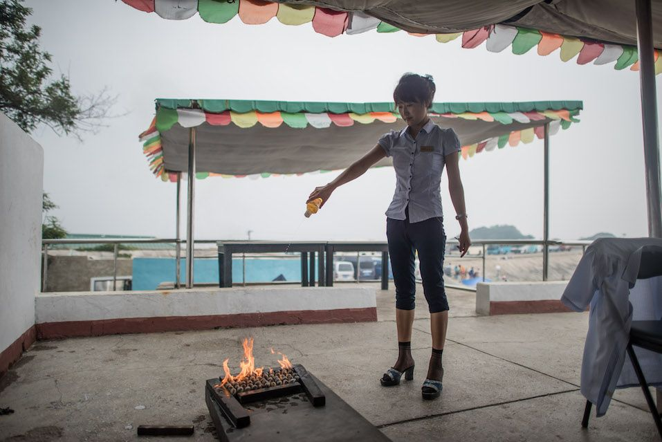 Hostess cooking clams using gasoline