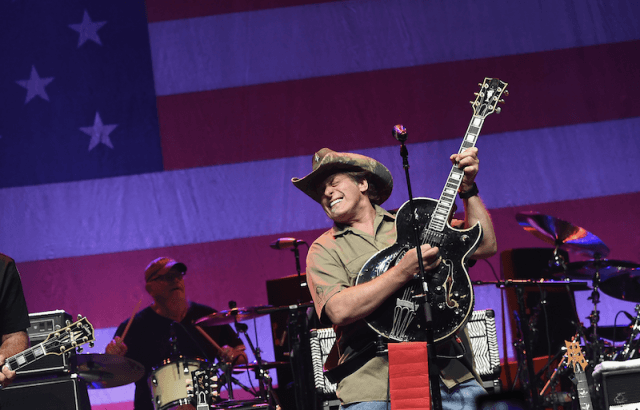 Ted Nugent performing on stage in front of a large American flag.