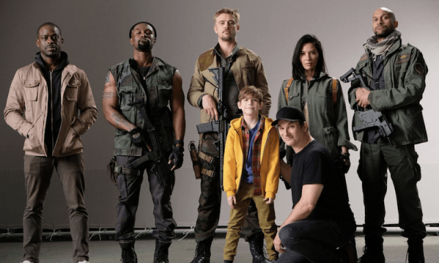 The cast of The Predator holding weapons and standing with a child.
