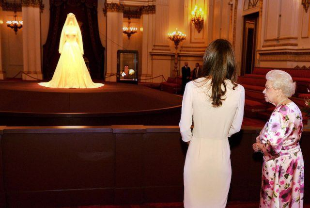 The Queen stands with Kate Middleton as they look at the Queen's wedding gown on display.