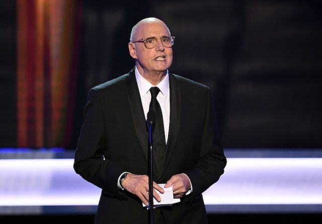 Jeffrey Tambor speaking in a suit in front of a microphone on stage.