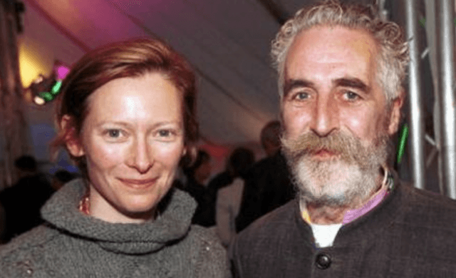 Tilda Swinton and John Byrne posing for a photograph at an event.