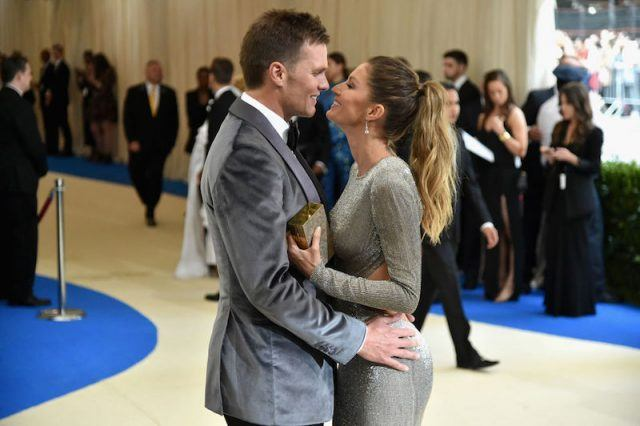 Tom Brady and Gisele Bundchan embracing and posing for the paparazzi.