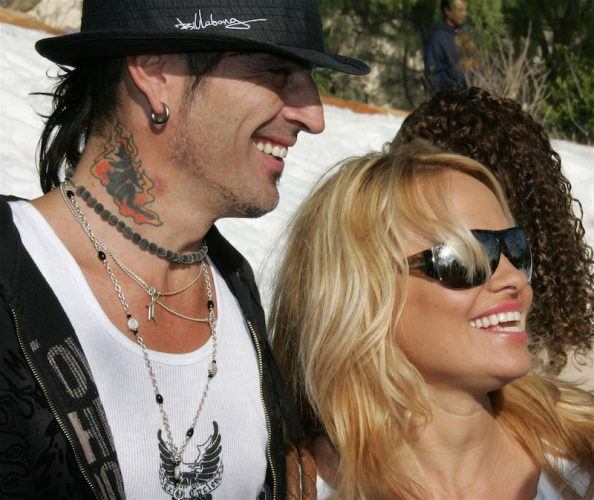 Tommy Lee and Pamela Anderson smiling while at a red carpet event.