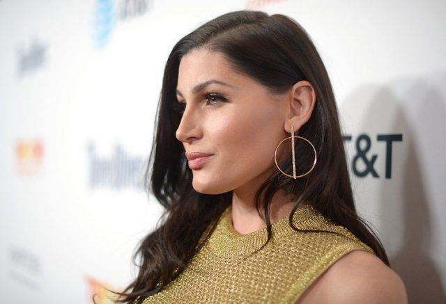 Trace Lysette poses in a gold dress and gold earrings.