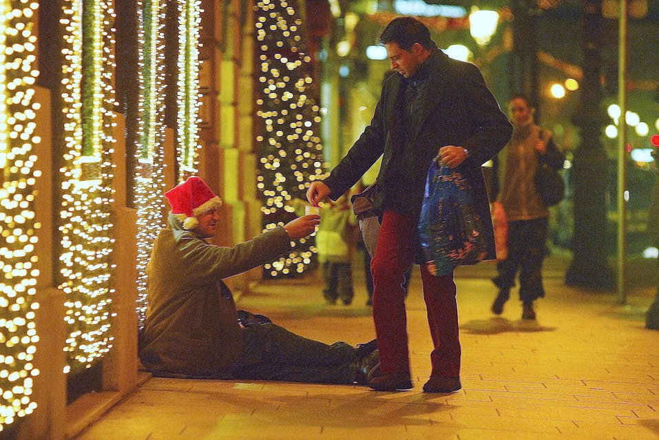 A man gives a homeless person some money in the street