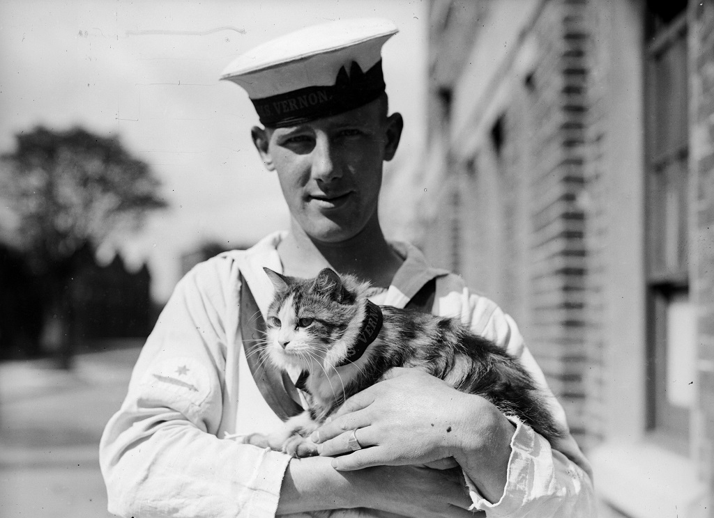 A sailor holds the ship's feline mascot, Minnie.