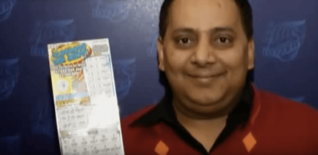 Urooj Khan holding up his winning lottery ticket.