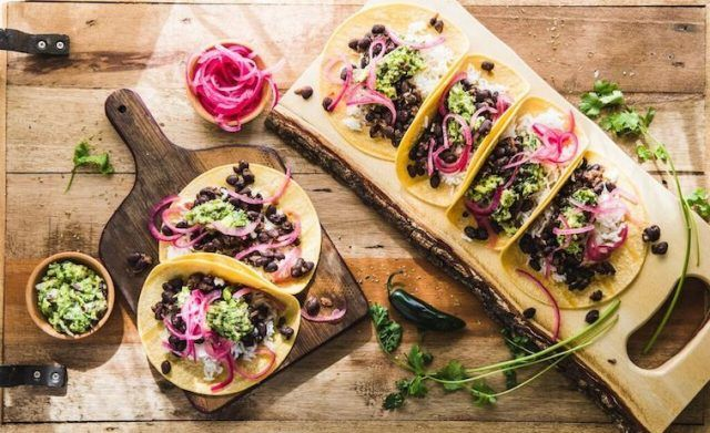 Black bean tacos on a wooden board and table.