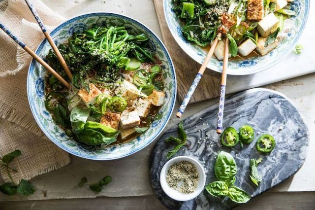 Tofu and vegetable pho in decorative bowls on a wooden table.